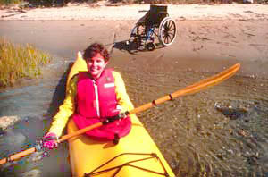 Lady in a kayak paddling away from the shore while behind her on the shore is an empty wheelchair.