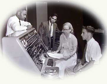 Admiral Grace Hopper, USN, with three other programmers at the control panel of the UNIVAC I computer.